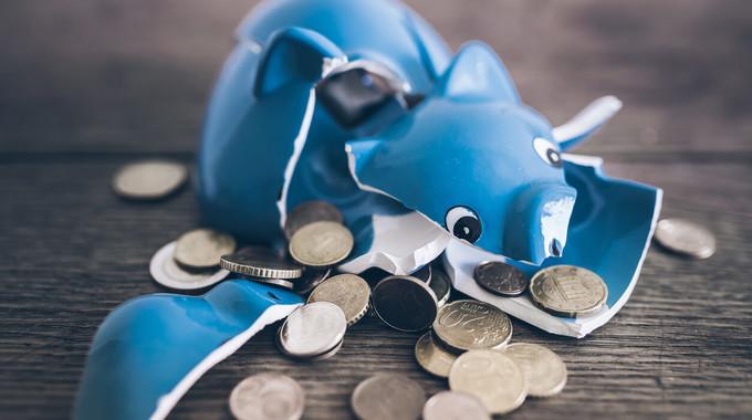 Zerschlagenes Sparschwein mit Münzen wegen Überschuldung